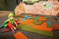 Toddler works floor puzzle in Backyard Adventures. Credit: Imagine Exhibitions, Inc.