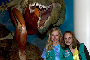 junior girl scout friends in front of the Albertasaurus