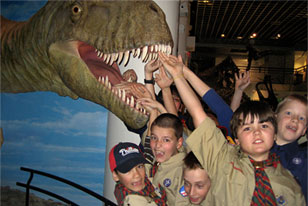 scouts posing with a dinosaur