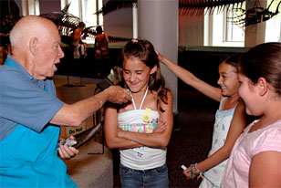 volunteer offering dino poop to young museum visitors