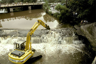 heavy machinery demolishing the low dam spanning the Manatawny
